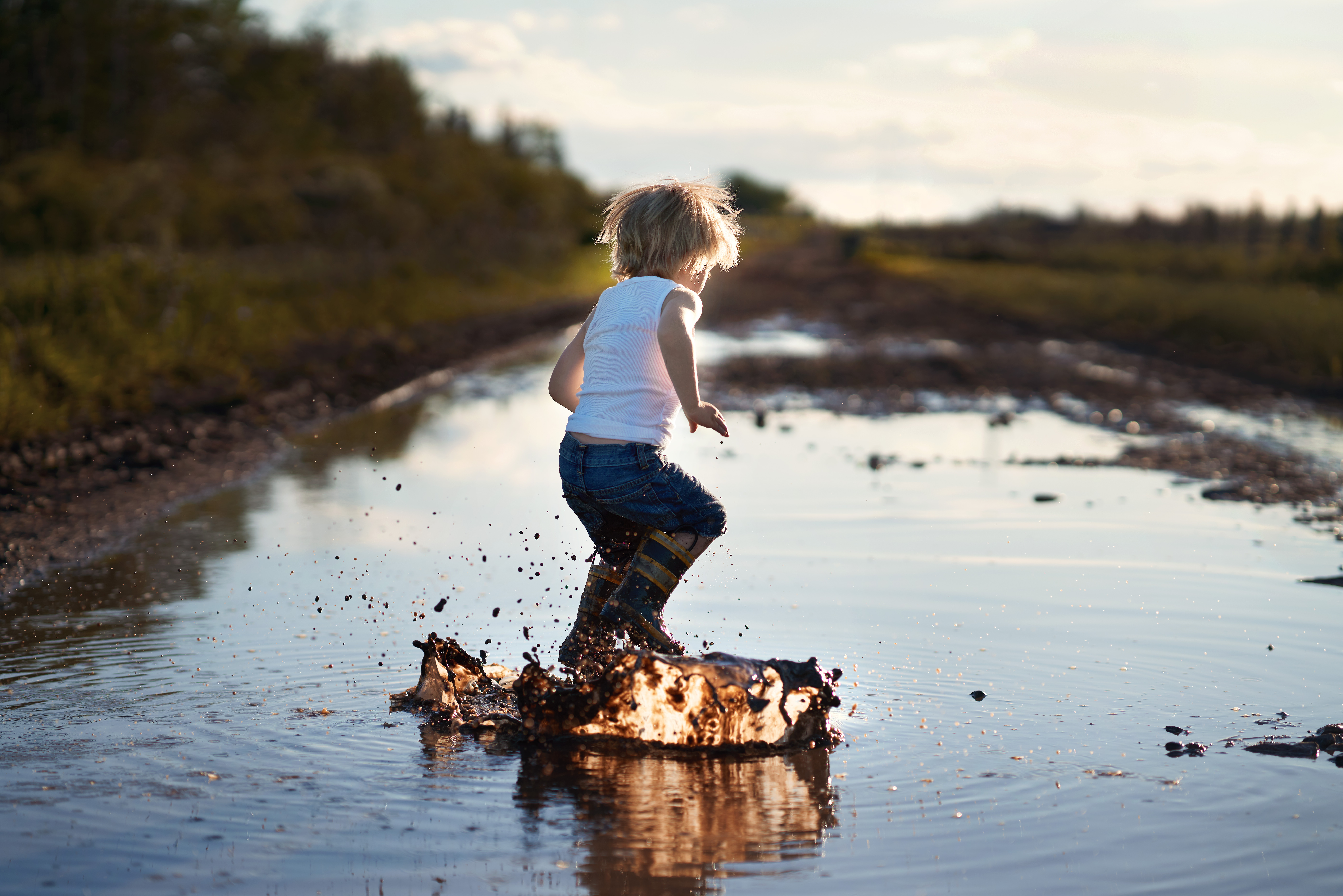 Photo of kid jumping in a puddle